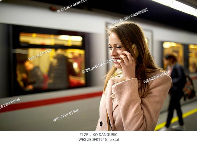 Austria, Vienna, smiling young woman on the phone at underground station platform
