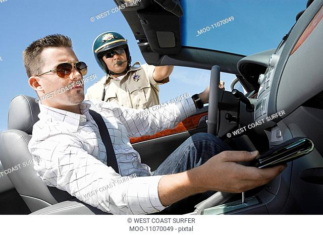 Man looking for driver licence while sitting in car