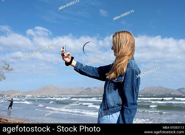 A 12-year-old girl stands between Pollenca and Alcudia on the beach and photographs herself with her mobile phone, kite surfers in the background