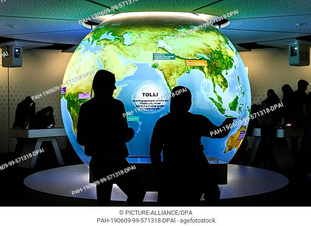 """29 May 2019, Bremen, Bremerhaven: In the """"""""World Future Lab"""""""" exhibition in the Klimahaus, two schoolgirls look at a large globe depicting the earth"""