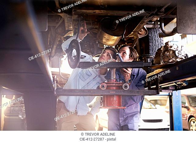 Mechanic and customer under car in auto repair shop
