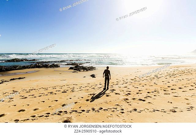 Coastal seascape of a faraway travelling man finding peace on a sunset beach. The lone explorer