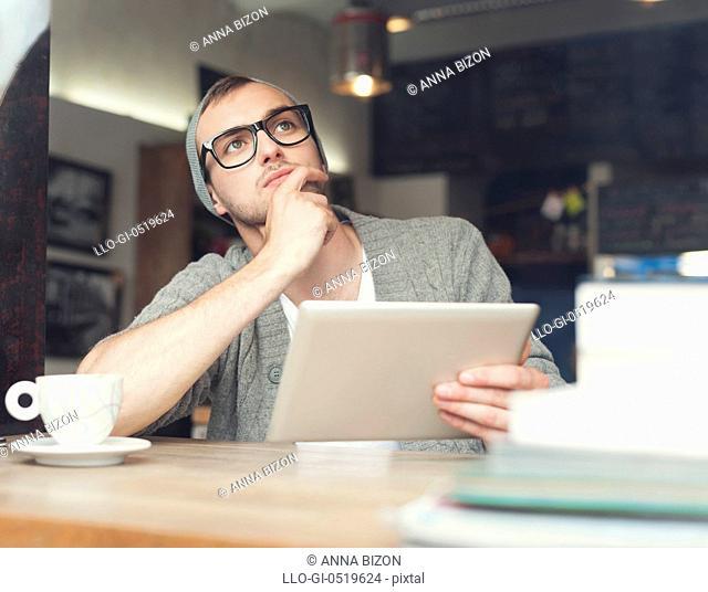 Dreaming man using digital tablet at cafe. Krakow, Poland
