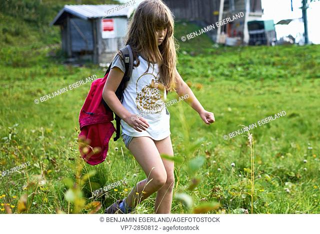 Young female child walking over green grass during hiking adventure in nature, Brauneck, Bavaria, Germany