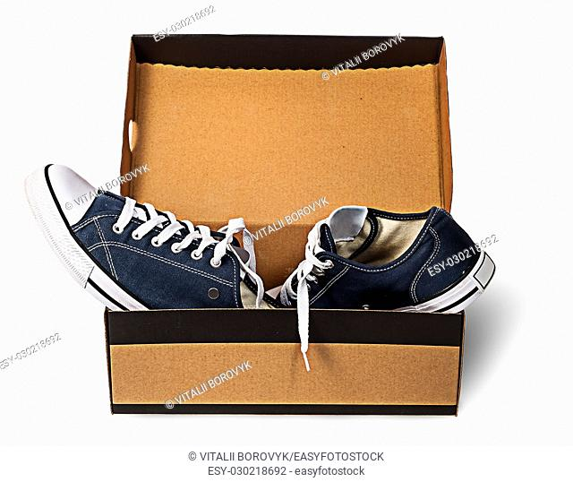Dark blue sports shoes abandoned in a cardboard box isolated on white background