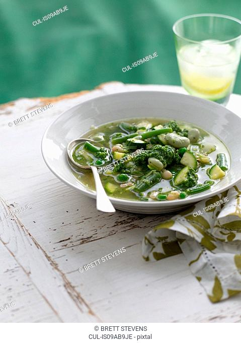 Bowl of spring pesto soup with zucchini and beans
