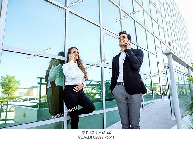 Smiling businesswoman and businessman on cell phones outside office building