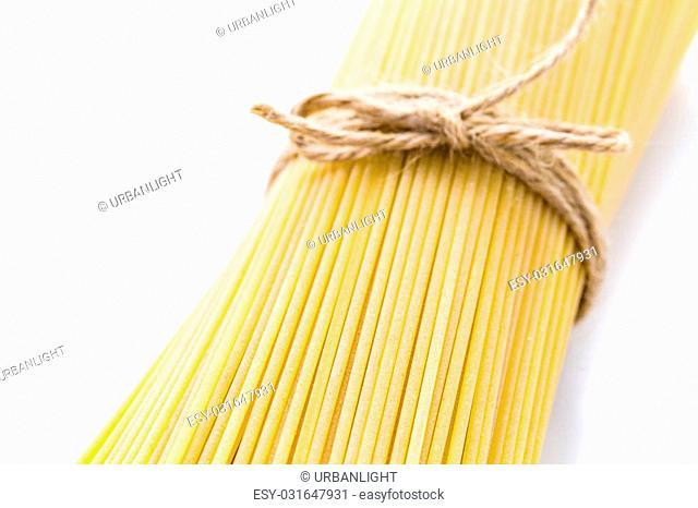 Organic yellow spaghetti pasta on a white background