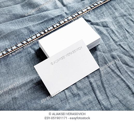 Blank name cards template. White paper business cards on denim background
