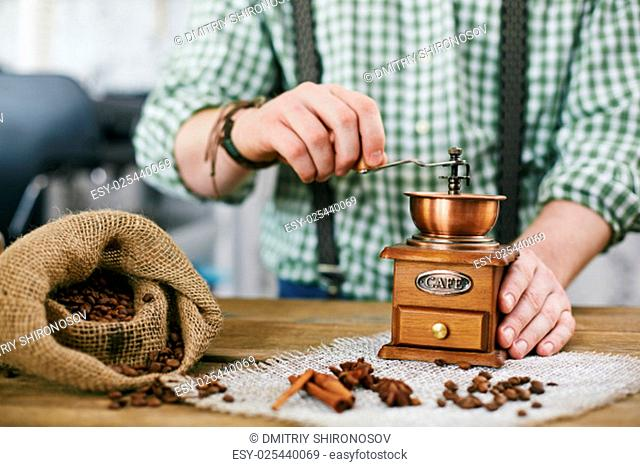 Barista tampering coffee beans in wooden coffee grinder