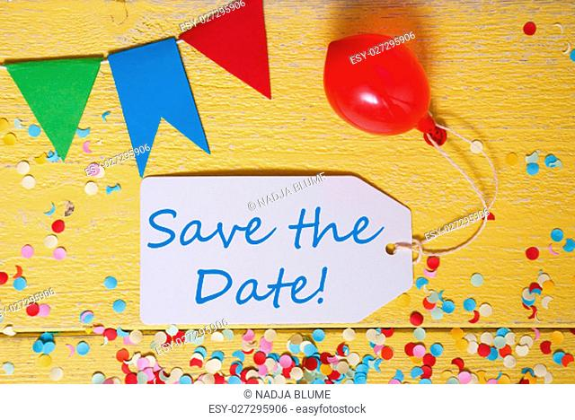 White Label With English Text Save The Date. Party Decoration Like Streamer, Confetti And Balloon. Flat Lay Or Top View. Yellow Wooden Background