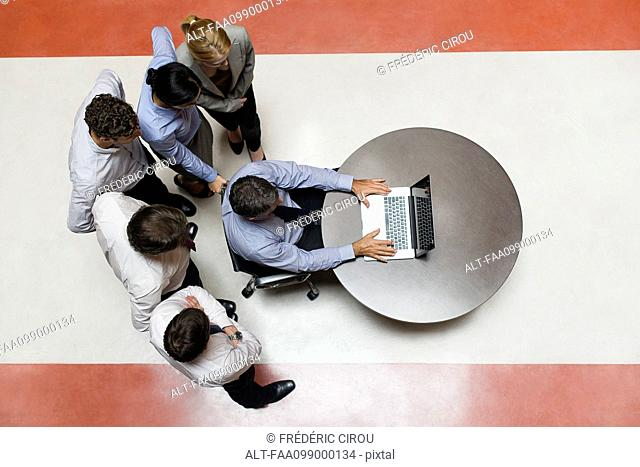 Businessman using laptop computer with colleagues standing by watching