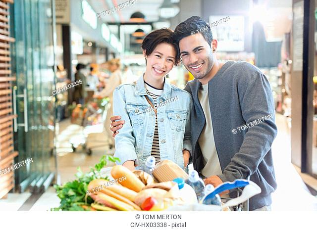 Portrait smiling young couple grocery shopping in market
