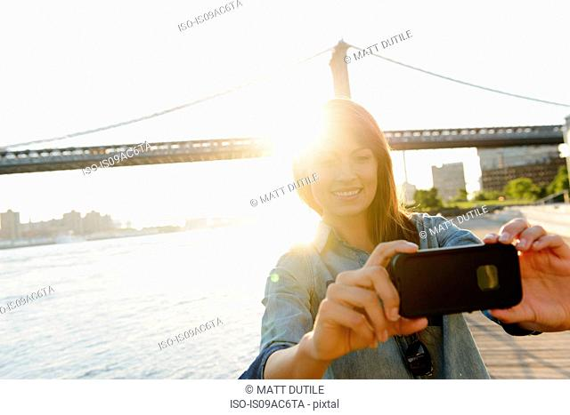 Young woman photographing herself with Manhattan Bridge, Brooklyn, USA