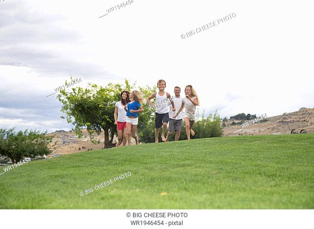 Family of five running up a grassy hill