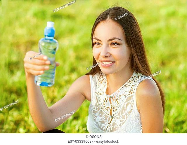 Portrait of young beautiful dark-haired woman wearing blue t-shirt drinking water at summer green park