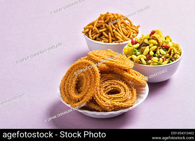Indian Snack : Chakli, chakali or Murukku and Besan (Gram flour) Sev and chivada or chiwada on pink background. Diwali Food