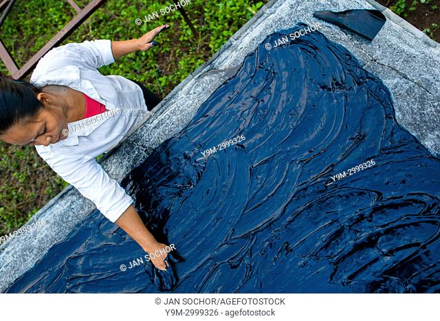 A Salvadoran farm worker spreads out the indigo paste onto a metal sheet table to dry in the sun at the semi-industrial manufacture near San Miguel, El Salvador