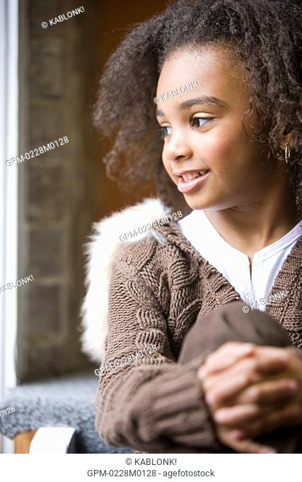 Portrait of young stylish African American girl sitting on stairs