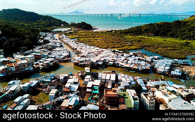 View of residential houses with boats moored in harbour, Hong Kong