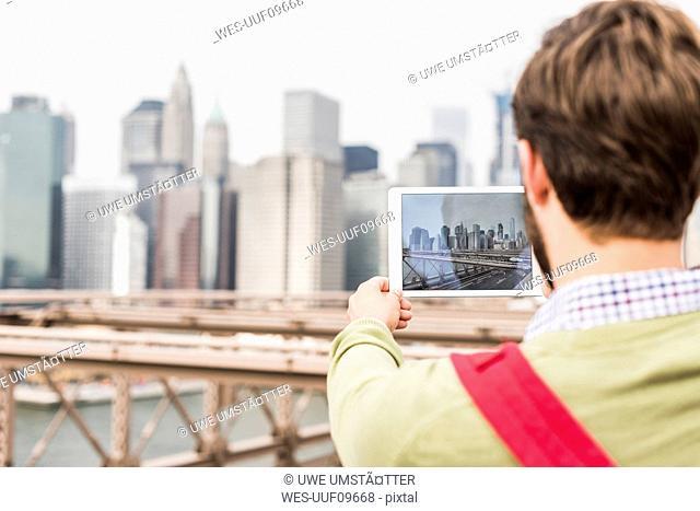 USA, New York City, man on Brooklyn Bridge taking tablet picture