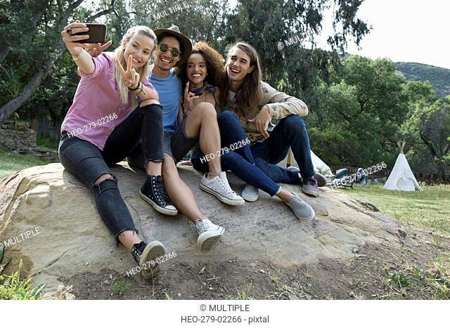Young friends taking selfie on rock outside campsite