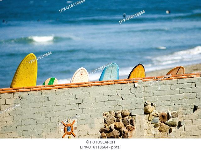 Surfboards leaning against the famous wall at Surf Rider Beach Malibu California USA