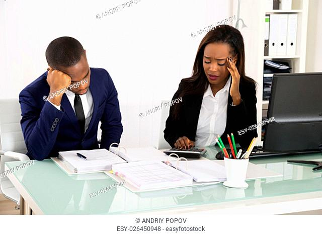 Two Worried African Businesspeople Sitting In Office