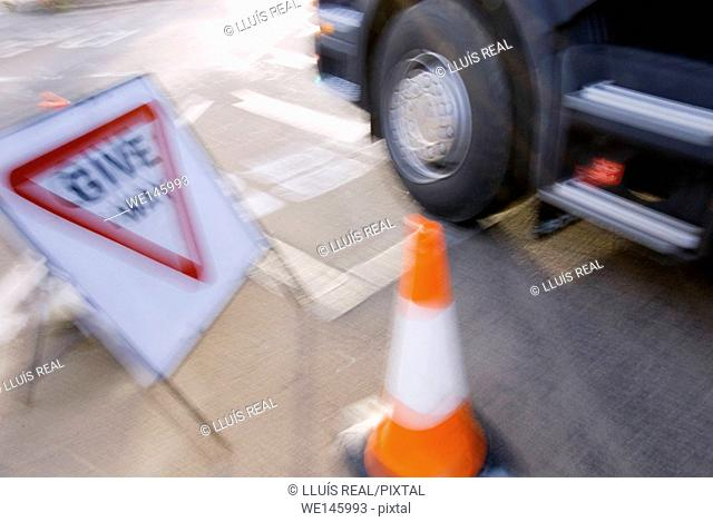 Blurred street scene. Give way sign, traffic cone and truck's wheel