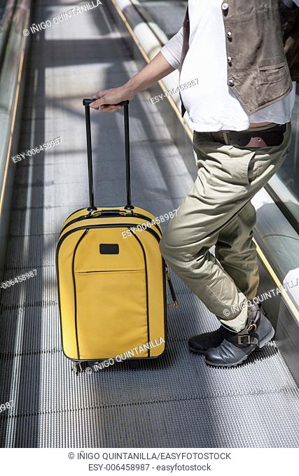 woman pregnant with yellow suitcase standing at walkway