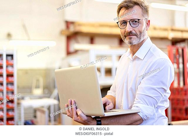 Portrait of confident businessman using laptop in factory