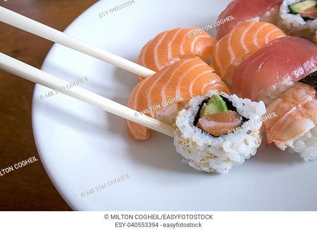 Fresh salmon nigiri sushi between chopsticks along with uramaki, prawn nigiri and tuna nigiri