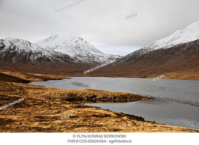 View across freshwater loch towards fishing hut, with snow covered mountain peak in background, Loch an t-Siob, Beinn a' Chaolais, Paps of Jura, Isle of Jura