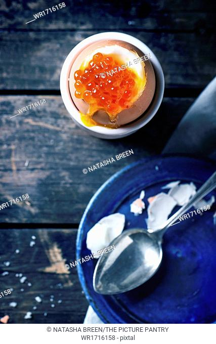 Breakfast with soft-boiled egg with red caviar in white eggcup, served with vintage spoon over old wooden table. See series