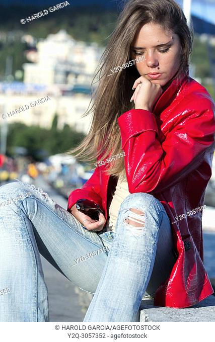 Beautiful woman in red jacket and jeans posing for the camera in different sensual positions in Yalta, Crimea