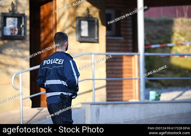 24 January 2020, Baden-Wuerttemberg, Rot Am See: After shots were fired in Rot am See in the north-east of Baden-Württemberg, a policeman is standing by a house