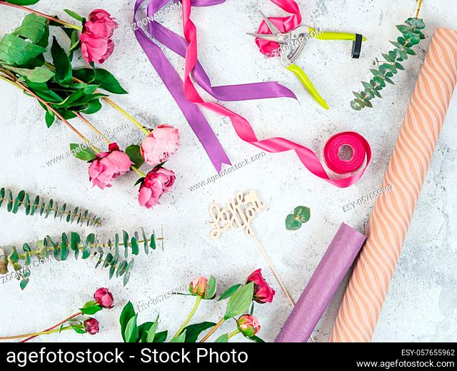 Floristic flat lay. Flowers, wrapping paper, ribbons and Love you wooden sign on gray tabletop. Roses, eucalyptus, Copy space