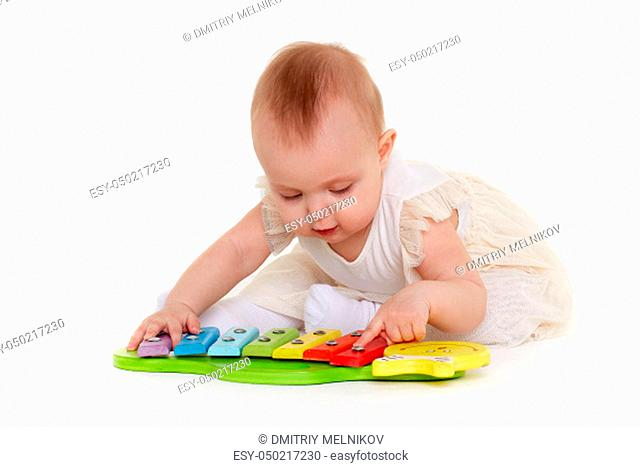 Sweet baby in dress plays with colourful xylophone (musical instrument toy for children) on a white background. Early development and learning toys