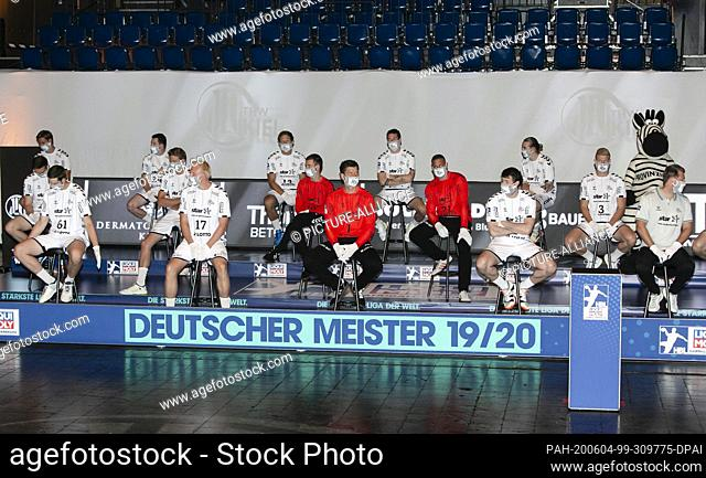 04 June 2020, Schleswig-Holstein, Kiel: The players of the German handball champion THW Kiel sit on a podium with distance and mouth-nose protection on bar...