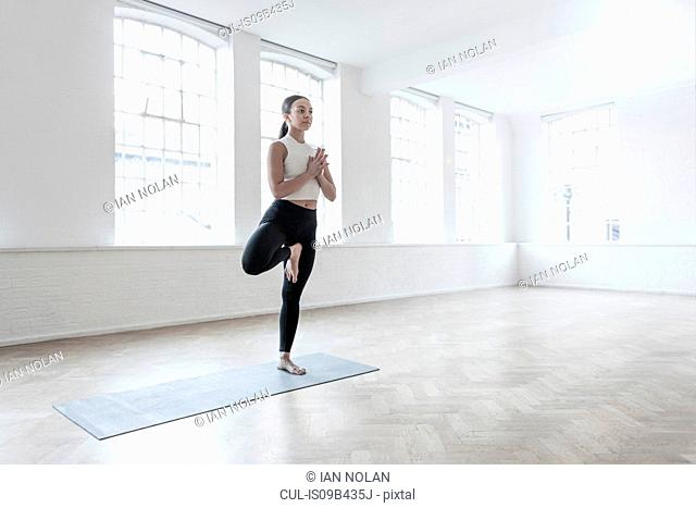 Woman in dance studio standing on one leg in yoga position