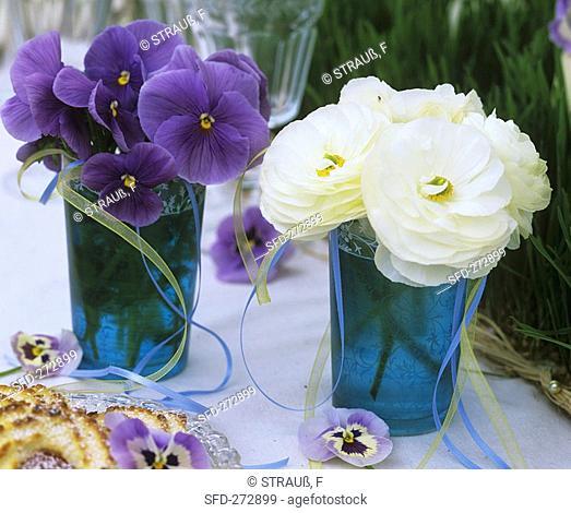 Pansies and Ranunculus in blue glasses