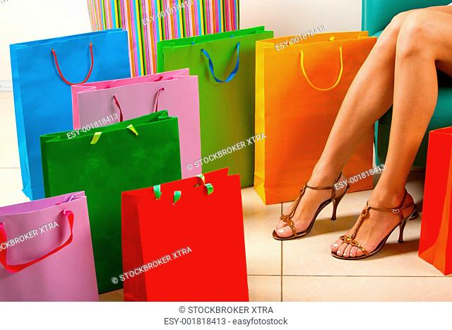 Legs of lady sitting surrounded by colorful paper bags