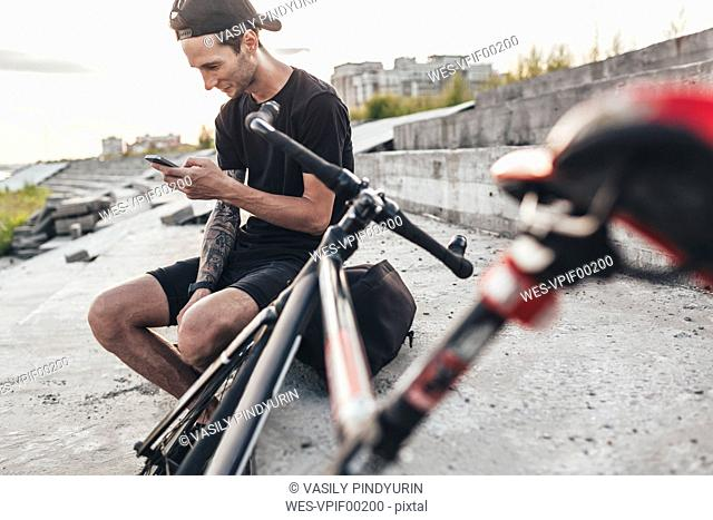 Young man sitting next to fixie bike using cell phone