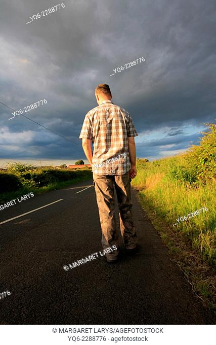 A man walking on the rural road in the golden sunlight