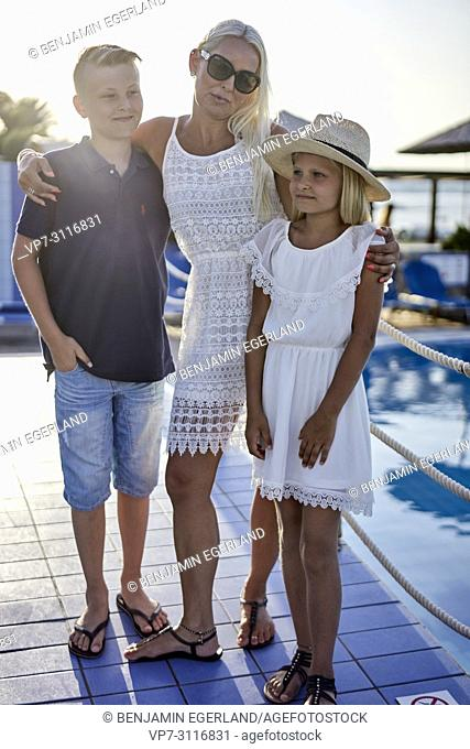 mother with two children next to pool, holiday