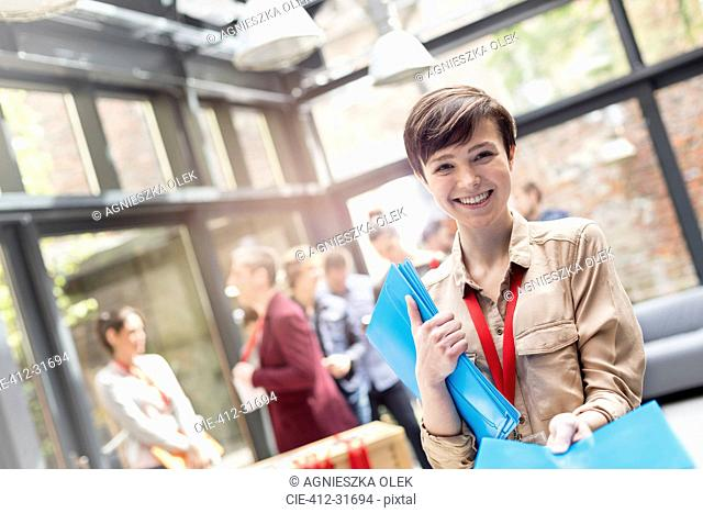 Portrait smiling young woman handing out packets at conference