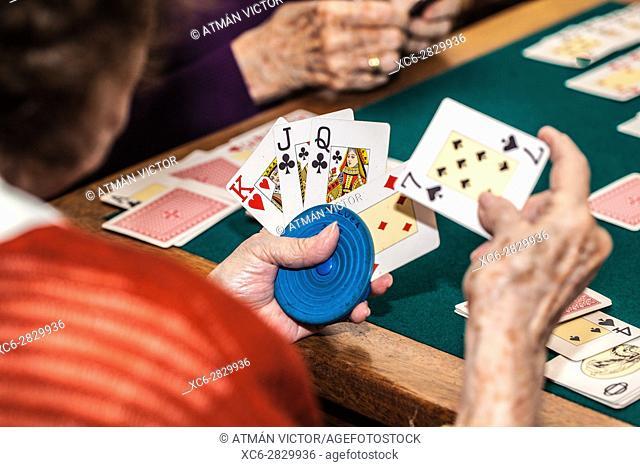 old women playing canasta game