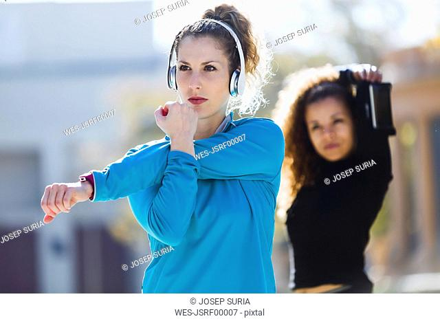 Two focused sportive young women stretching listening to music