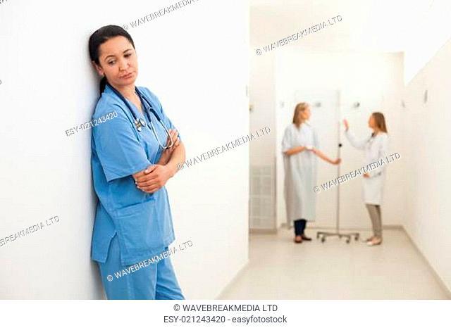 Nurse feeling sad with doctor talking to patient in hospital corridor