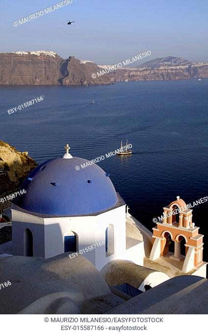 Traditional church in Oia Santorini Greece view of a sailing ship in the Caldera